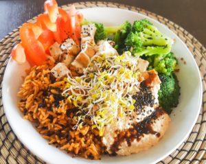 Bowl mit Reis, Paprika, Brokkoli, Tofu, Hummus und Sprossen
